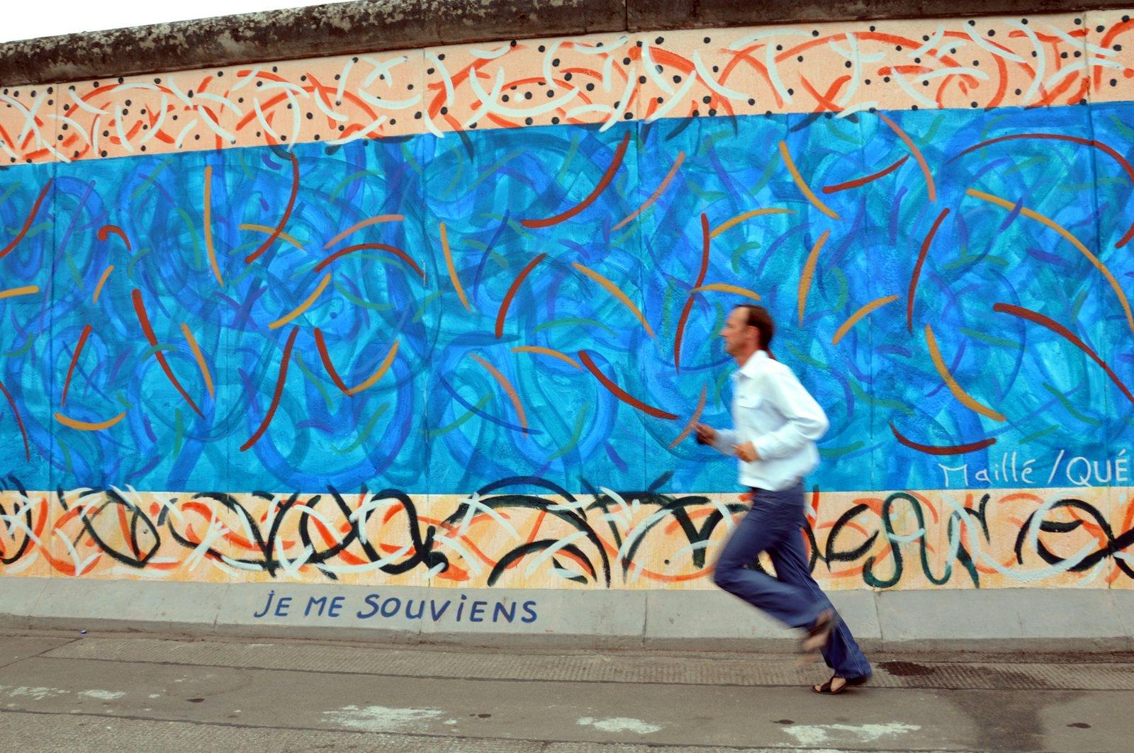 Un hombre corre fuera de la East Side Gallery en 2010...