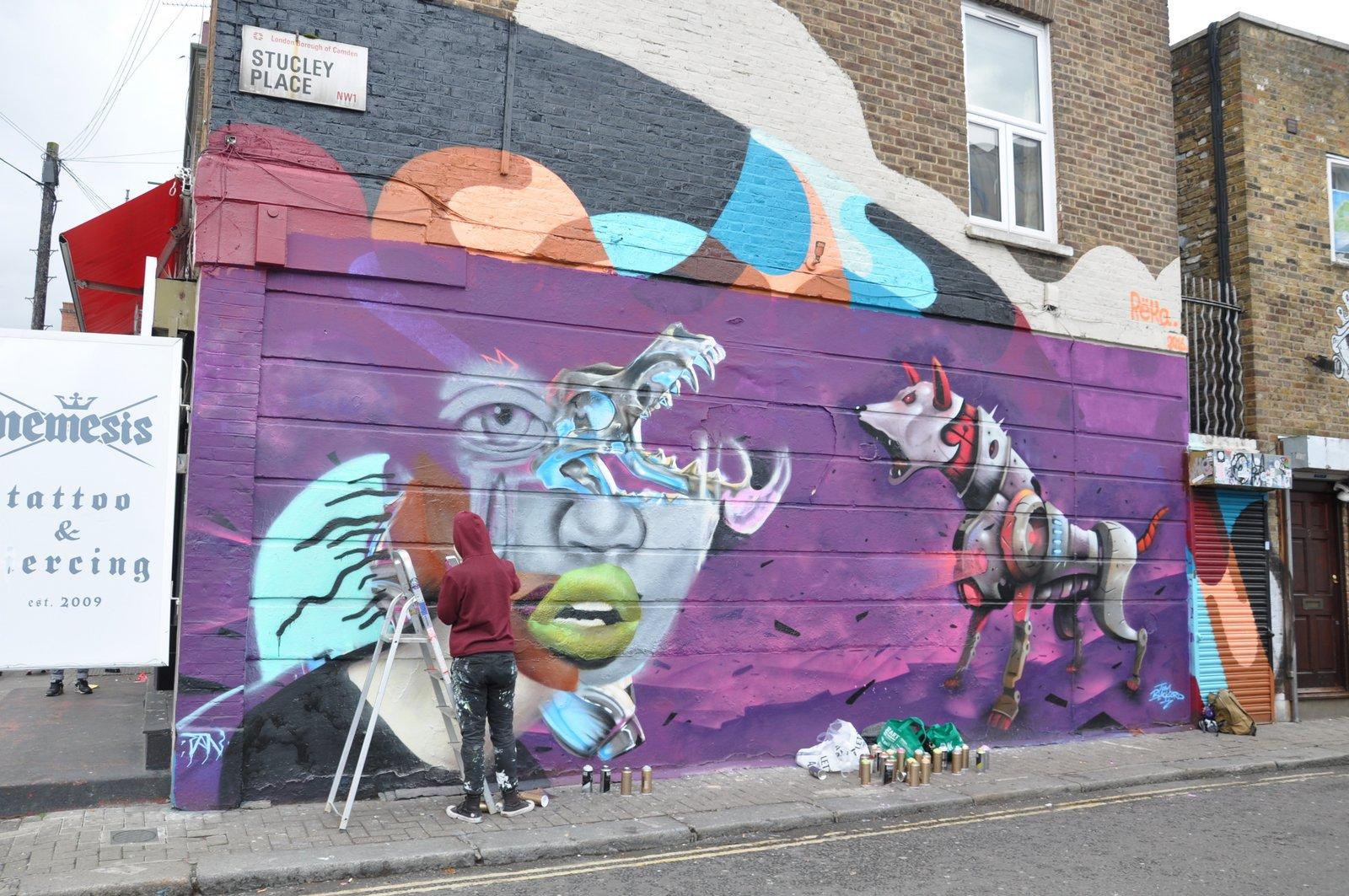 Un fresco de arte callejero pronto fue reemplazado por otro... aquí un artista en el trabajo