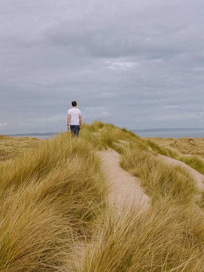 el hombre camina por un sendero de dunas altas con pastos largos