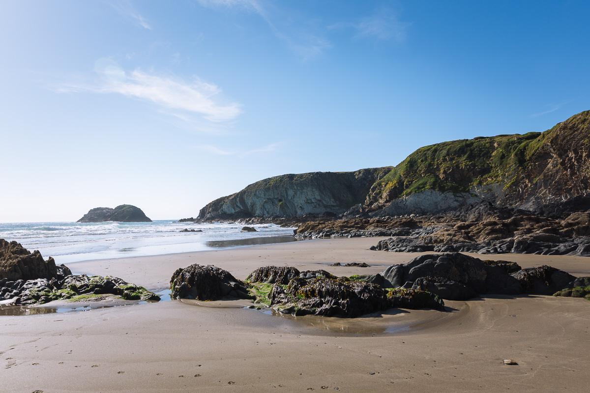 playa de arena rodeada de acantilados con grandes rocas