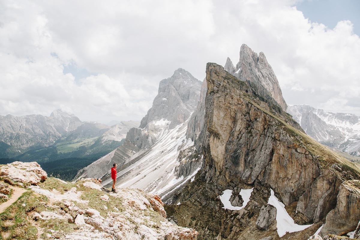el hombre se encuentra frente a los picos irregulares dramáticos en los Dolomitas