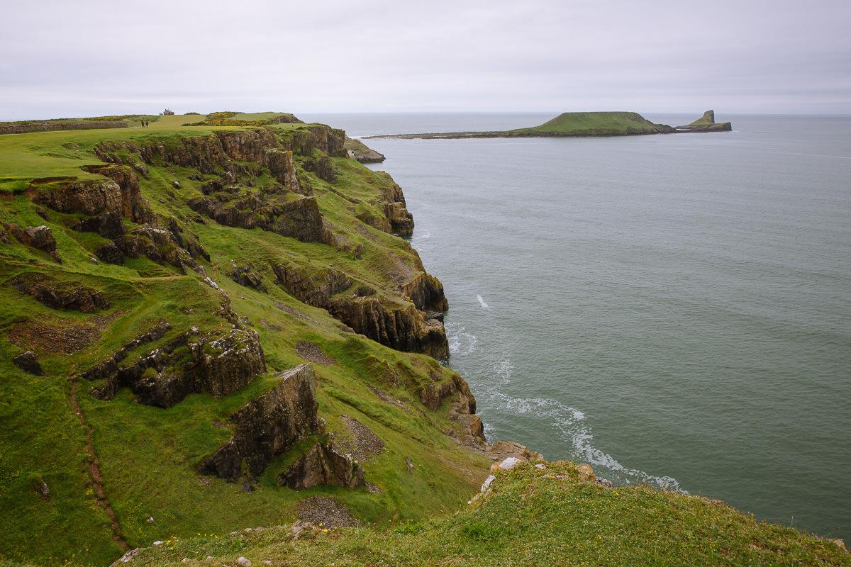 costa verde escarpada con promontorio de cabeza de gusano en el fondo