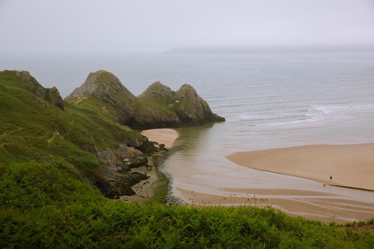 3 picos de piedra caliza frente a una gran franja de arena dorada en el mar