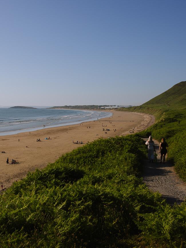personas caminando por un camino a una amplia playa de arena