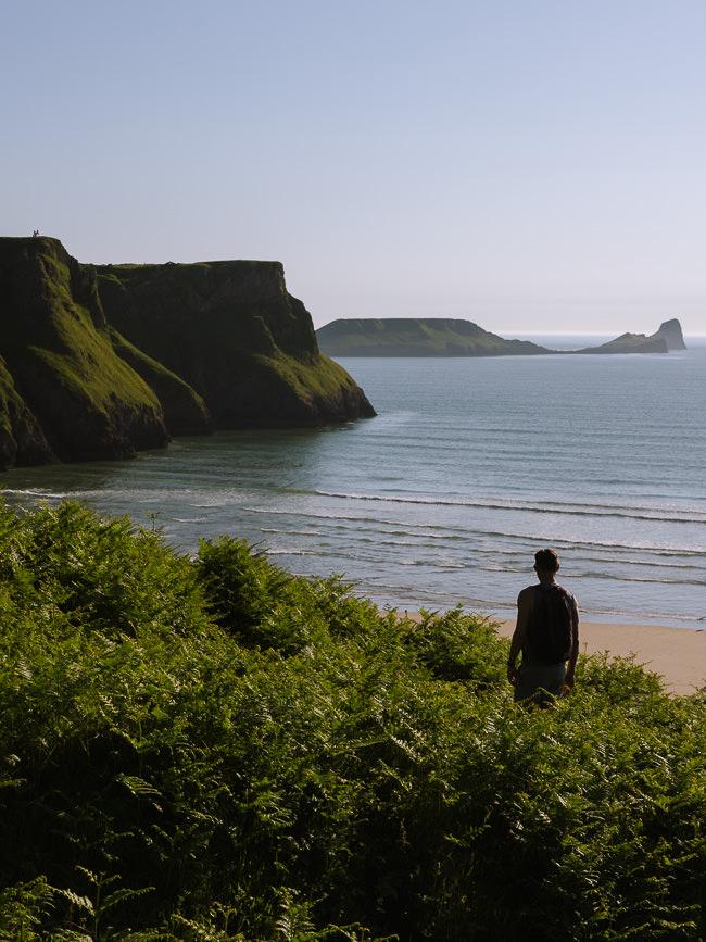 de pie frente a una hermosa playa de arena con acantilados cubiertos de hierba en el fondo