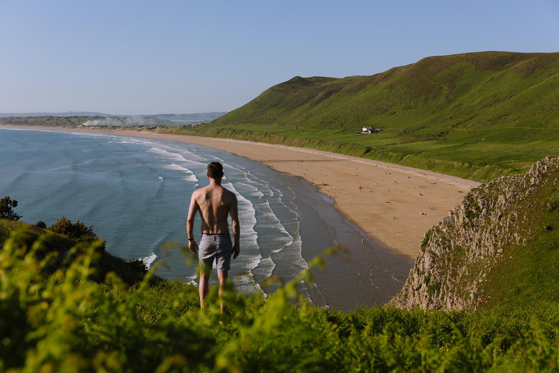 De pie sobre un acantilado con vistas a una gran playa de arena con colinas verdes en el fondo