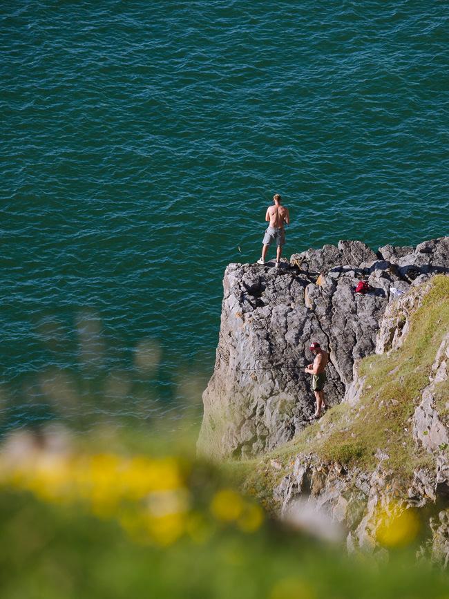 pescador de pie en una cornisa rocosa con el mar a continuación