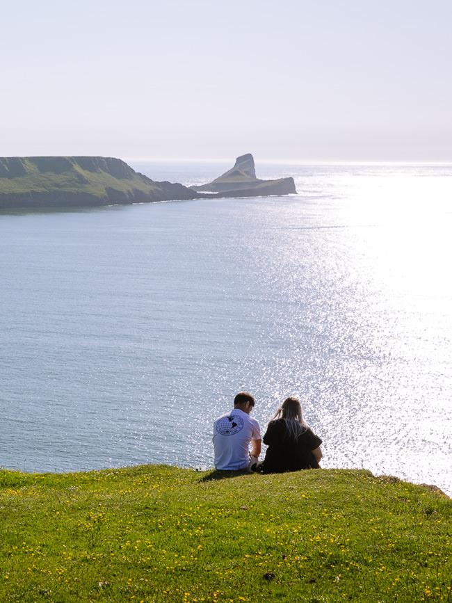 pareja se sienta en un acantilado con vistas a un promontorio rocoso
