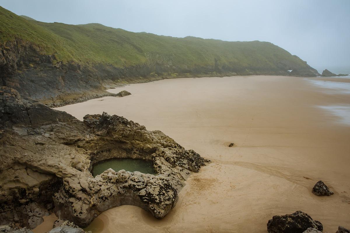 piscina de roca circular en una amplia playa de arena