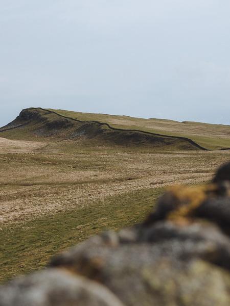 Una larga muralla romana se extiende hasta la distancia en el Paseo de la Muralla de Adriano