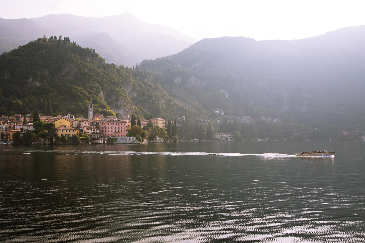 Una lancha rápida sale de un pueblo colorido escondido en las montañas en el lago de Como