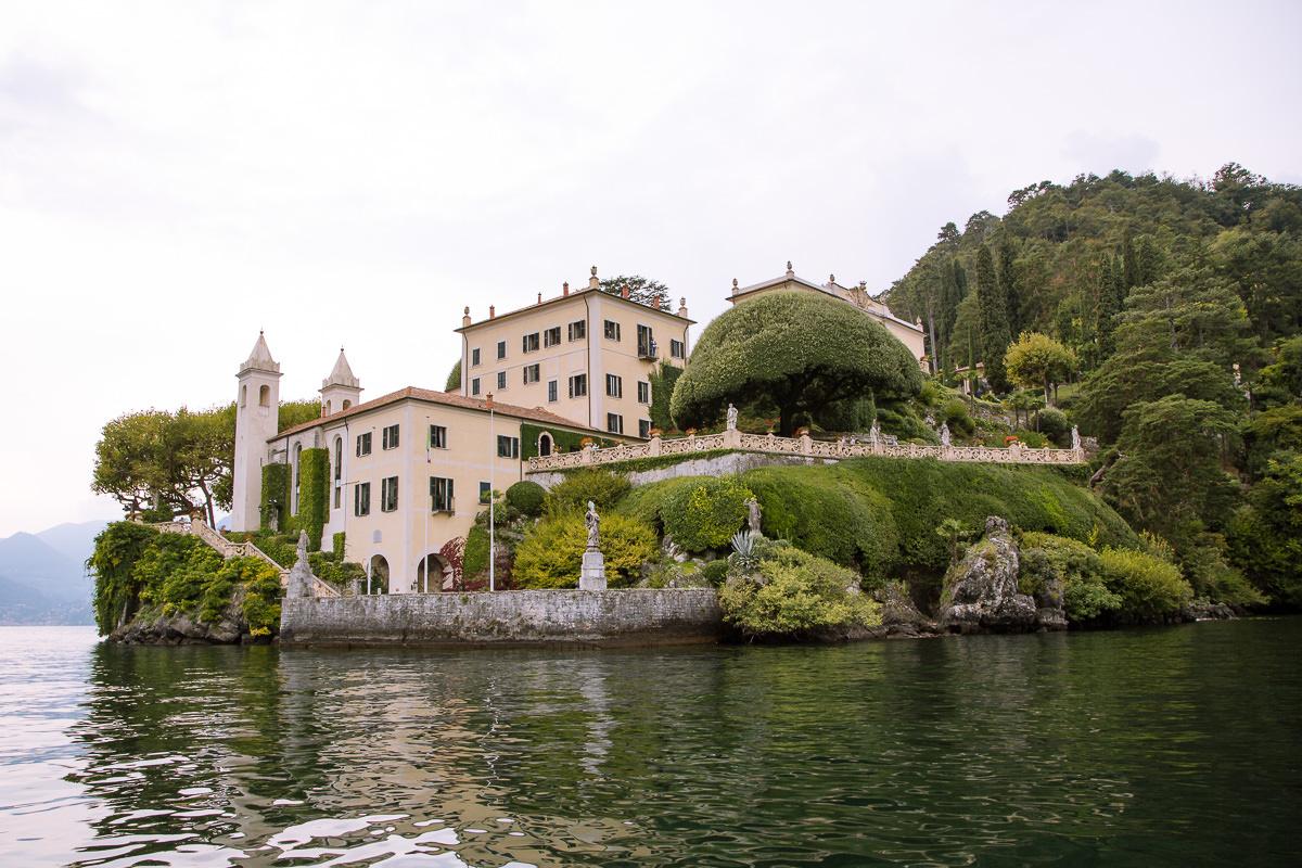 mansión con jardín cuidado situado al lado de un lago.