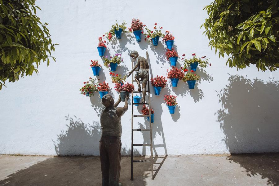 Estatua de un hombre pasando una planta de maceta a un niño en una escalera