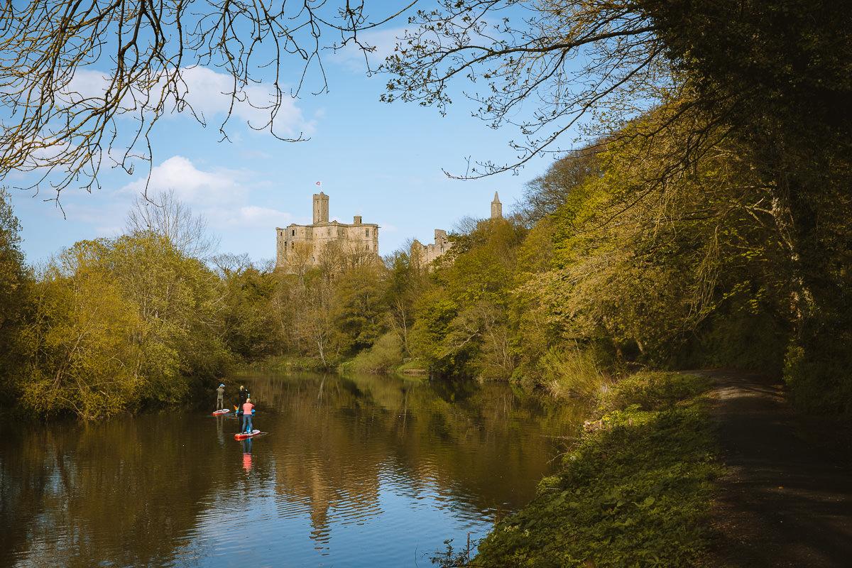 río tranquilo rodeado de árboles frente a un antiguo castillo