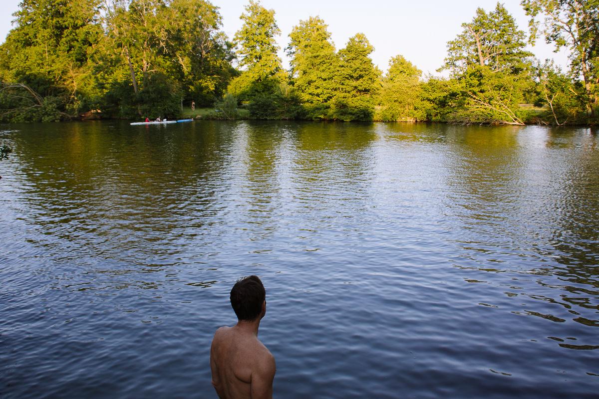 hombre nadando en la luz de la tarde en un río ancho