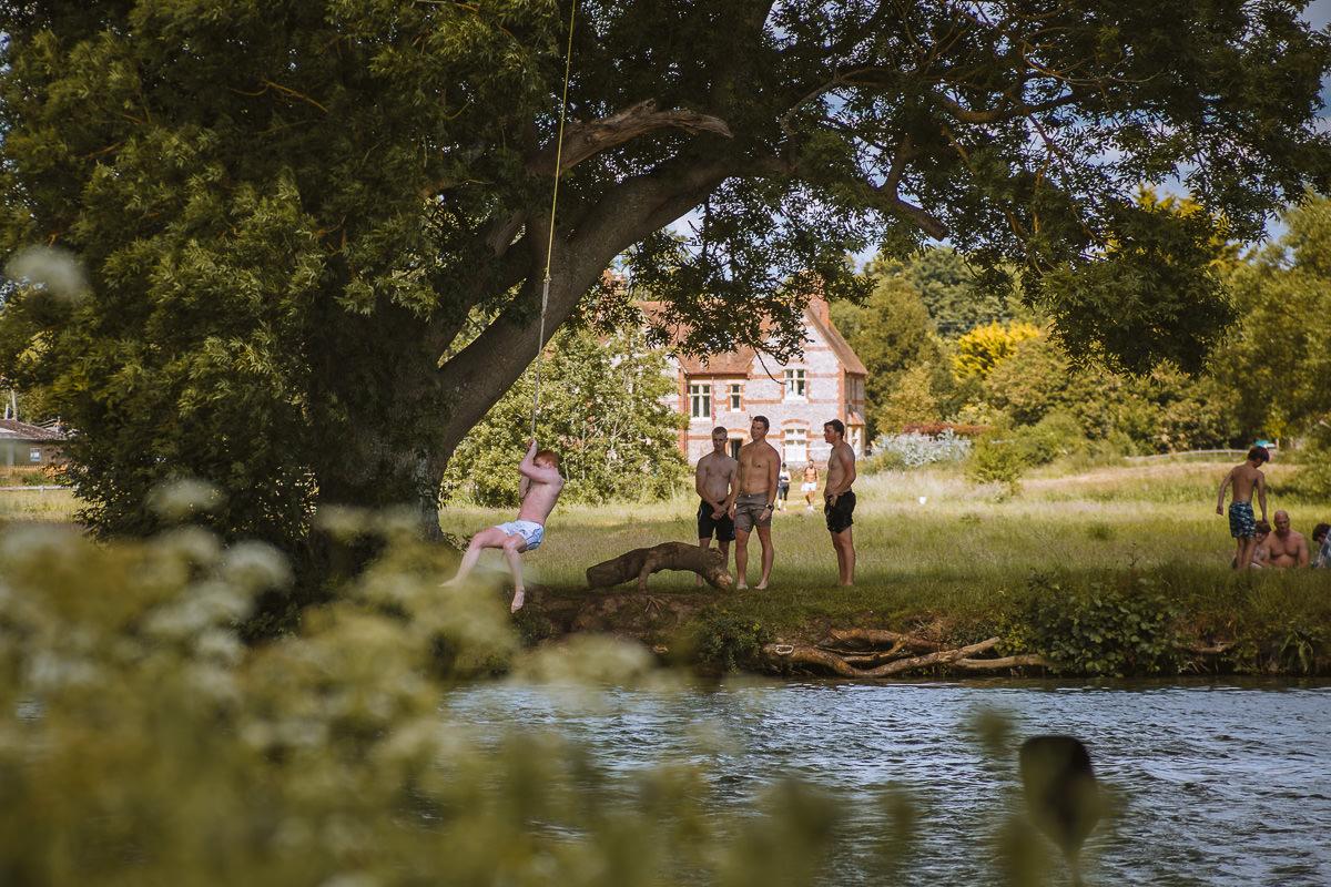grupo de niños columpio en una cuerda en un río