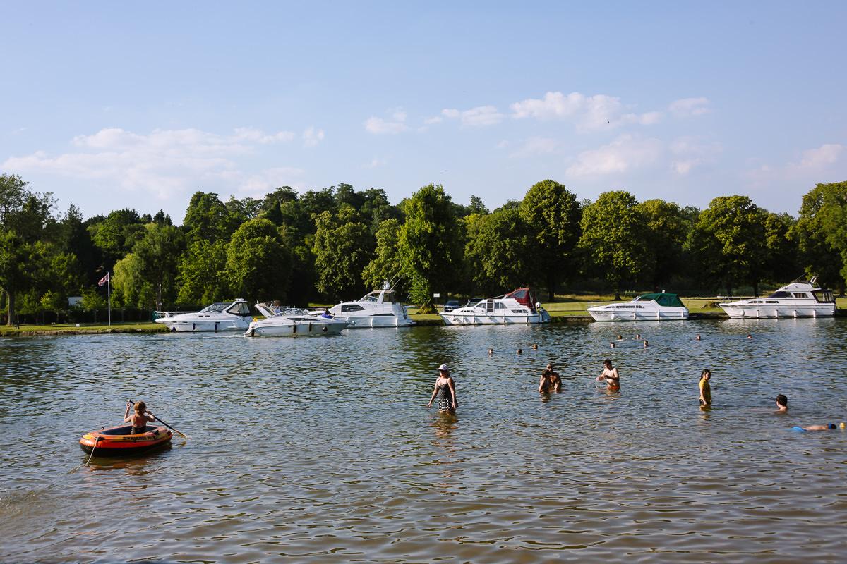 nadadores en un río con barcos en el otro lado