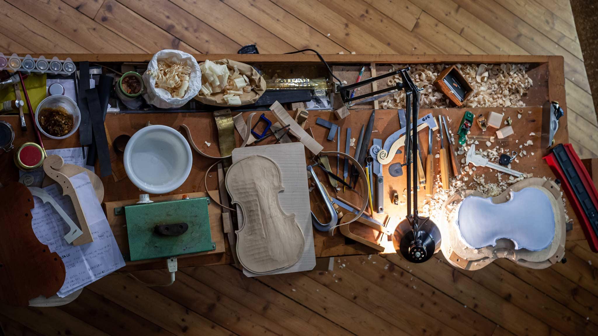 Mirando hacia abajo sobre una mesa donde los violines están llenos de varias herramientas en Cremona