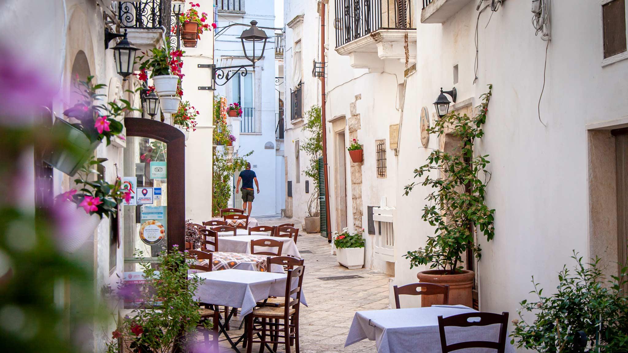 Un restaurante al aire libre en las calles blancas de Locorotondo Puglia