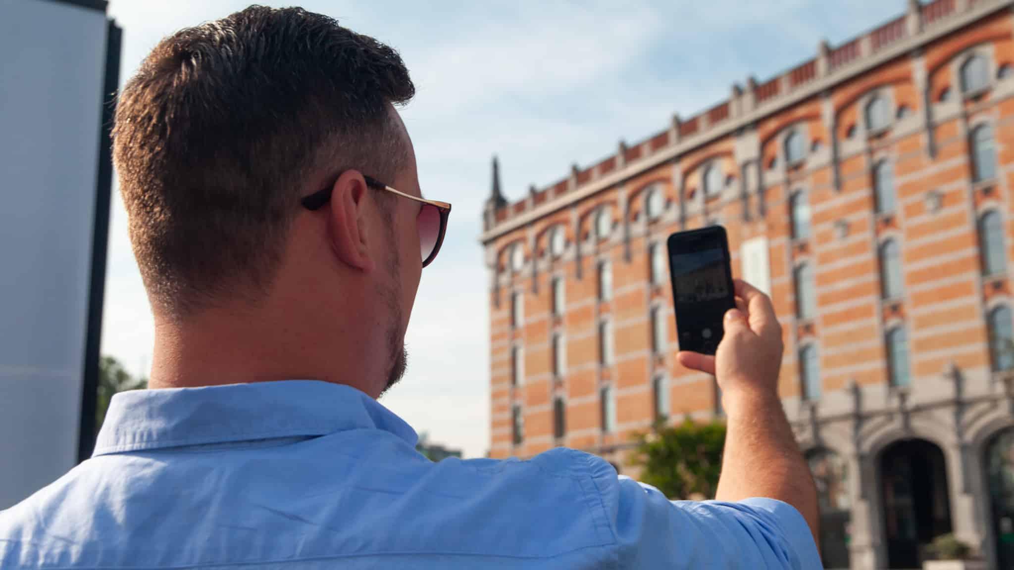 Dan usando un teléfono móvil para tomar una foto en Bruselas