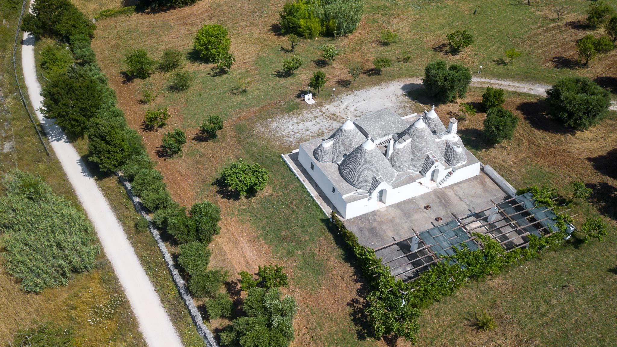 Un Trulli house hotel visto desde arriba rodeado de olivos